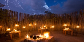 Ngama Tented Safari Lodge outside dining restaurant, the boma. Fire, Lanterns and the night's sky